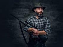 A hunter holds a rifle. Studio portrait of bearded hunter male wearing a plaid fleece shirt holds a rifle Stock Image