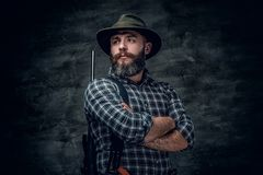 A hunter holds a rifle. Studio portrait of bearded hunter male wearing a plaid fleece shirt holds a rifle Royalty Free Stock Photos