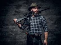 A hunter holds a rifle. Studio portrait of bearded hunter male wearing a plaid fleece shirt holds a rifle Royalty Free Stock Images