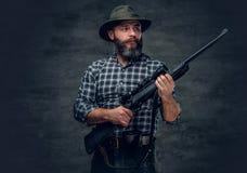 A hunter holds a rifle. Studio portrait of bearded hunter male wearing a plaid fleece shirt holds a rifle Royalty Free Stock Photo