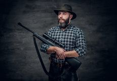 A hunter holds a rifle. Studio portrait of bearded hunter male wearing a plaid fleece shirt holds a rifle Royalty Free Stock Photography