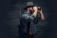 A hunter holds a rifle. Studio portrait of bearded hunter male wearing a plaid fleece shirt looking through binoculars, holds a rifle Stock Photos