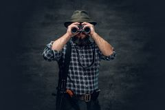 A hunter holds a rifle. Studio portrait of bearded hunter male wearing a plaid fleece shirt looking through binoculars, holds a rifle Royalty Free Stock Photography