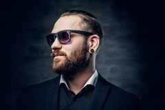 Studio portrait of bearded male dressed in a blue jacket and sunglasses. Studio portrait of bearded male dressed in a blue jacket and sunglasses over dark grey Stock Photos