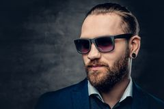 Studio portrait of bearded male dressed in a blue jacket and sunglasses. Studio portrait of bearded male dressed in a blue jacket and sunglasses over dark grey Stock Photography