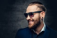 Studio portrait of bearded male dressed in a blue jacket and sunglasses. Studio portrait of bearded male dressed in a blue jacket and sunglasses over dark grey Stock Images
