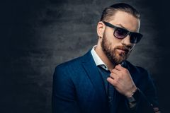 Studio portrait of bearded male dressed in a blue jacket and sunglasses. Stylish bearded male in sunglasses over dark grey background Stock Photo
