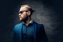 Studio portrait of bearded male dressed in a blue jacket and sunglasses. Stylish bearded male in sunglasses over dark grey background Royalty Free Stock Photos