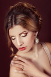 Studio portrait of a beautiful dark blond woman with evening hairdo and makeup. Wearing precious jewellery stock images