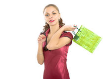 Studio portrait of the beautiful girl. The girl in a red dress with a gift in hands stock images