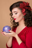 Studio portrait of a beautiful girl with blue Christmas ball in the hands of Royalty Free Stock Photo
