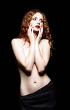 Studio portrait of beautiful red-haired woman on black background Stock Photos