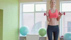 Studio portrait of a beautiful sporty muscular woman working out with two dumbbells.  stock video