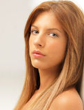 Studio portrait beautiful woman leaning on wall Stock Images