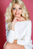 Studio portrait of a beautiful woman. With long blonde curly hair,blue eyes,pink lipstick,light makeup,gold earrings in her ears,dressed in a short white dress royalty free stock photo