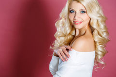 Studio portrait of a beautiful woman. With long blonde curly hair,blue eyes,pink lipstick,light makeup,gold earrings in her ears,dressed in a short white dress royalty free stock image