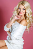 Studio portrait of a beautiful woman. With long blonde curly hair,blue eyes,pink lipstick,light makeup,gold earrings in her ears,dressed in a short white dress stock photography