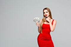 Studio portrait of beautiful woman in red dress holds the money, thinks where to spend it. Young slender girl with. Studio portrait of beautiful woman in red Royalty Free Stock Photos