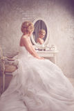 Studio portrait of beautiful young bride in white dress looking Royalty Free Stock Photography