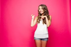 Pretty girl with stunning hairstyle showing direction. Studio portrait of beautiful young girl with gorgeous hairstyle wearing white top and denim shorts royalty free stock photography