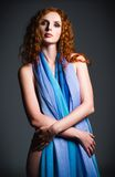 Studio portrait of beautiful young red-haired woman covered in cloth Stock Photos