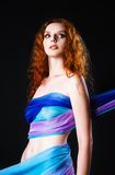 Studio portrait of beautiful young redhead woman covered in fabric Stock Images