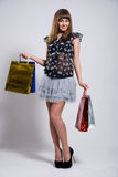 Studio portrait of a beautiful young woman. In a colourful outfit, holding in her hands a few shopping bags Royalty Free Stock Photo