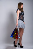 Studio portrait of a beautiful young woman. In a colourful outfit, holding in her hands a few shopping bags Stock Images