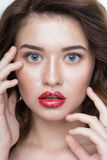 Studio portrait of a beautiful young woman. Fashion Makeup Model with perfect makeup, red lips and smooth, clean skin. Highlighter Royalty Free Stock Photo