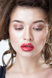 Studio portrait of a beautiful young woman. Fashion Makeup Model with perfect makeup, red lips and smooth, clean skin. Highlighter Royalty Free Stock Image