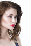 Studio portrait of a beautiful young woman. Fashion Makeup Model with perfect makeup, red lips and smooth, clean skin. Highlighter Stock Image