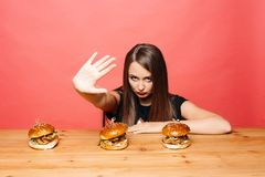 Woman protesting against burgers. Royalty Free Stock Image