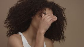 Studio portrait of black model woman looking at camera, ideal skin concept