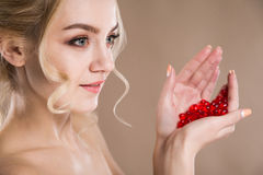 Studio portrait of a blonde in her hands red capsules of vitamin Stock Image