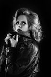 Studio portrait of blonde woman in leather biker jacket. Royalty Free Stock Photos
