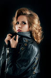 Studio portrait of blonde woman in leather biker jacket. Royalty Free Stock Image