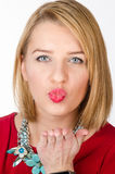 Studio portrait of a blonde woman sending an air kiss Royalty Free Stock Photo