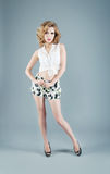 Studio portrait of blonde woman in shorts and white blouse. Sexy Stock Image