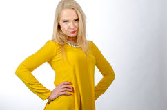 Studio portrait of a blonde woman wearing yellow dress Royalty Free Stock Image