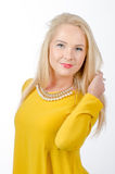 Studio portrait of a blonde woman wearing yellow dress Royalty Free Stock Photography