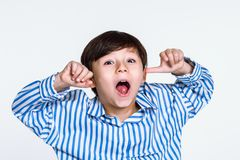 Studio portrait of a boy staring at the camera and acting up. Shot Stock Images