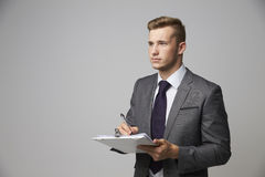 Studio Portrait Of Businessman Writing On Clipboard Stock Images