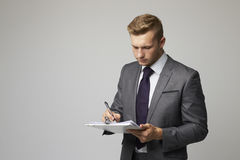 Studio Portrait Of Businessman Writing On Clipboard Royalty Free Stock Images