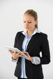Studio Portrait Of Businesswoman Standing Against White Background Using Digital Tablet Royalty Free Stock Photo
