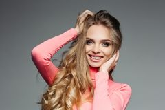 Studio portrait of a cheerful beautiful girl with long blonde wavy and thick hair and professional make-up wearing a. Pink blouse, holding hands on her hair and royalty free stock photos