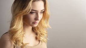 studio portrait of a confident young woman, girl face with curly hair disheveled from wind , the concept of natural beauty, stock photography