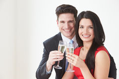 Studio Portrait Of Couple Celebrating With Champagne Stock Photography