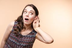 Charming girl listening to gossips. Studio portrait of beautiful caucasian. Studio portrait of curious brunette girl in multicolored top listening to the news or royalty free stock photography