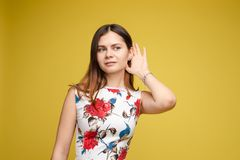 Charming girl listening to gossips. Studio portrait of beautiful caucasian. Studio portrait of curious brunette girl in multicolored top listening to the news or stock photos