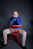 Studio portrait of a cute blond girl sitting on a red chair Stock Photo